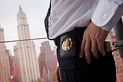 Official NYC shield belonging to Investigative Engineering Services, Assistant Commissioner Tim Lynch inspecting a new construction site in Manhattan, New York City. A detail of his department badge, Tim works in the prevention of damage to old and ensuring new buildings are up to standard plus often, assessing the status of a collapsed structure. From the chapter entitled 'The Skyline' and from the book 'Risk Wise: Nine Everyday Adventures' by Polly Morland (Allianz, The School of Life, Profile Books, 2015).