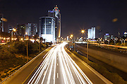 Israel, Tel Aviv, Long exposure Night shot of Ayalon highway looking south with Sherton City Tower on the left and Azrieli high rises on the far right