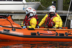 © Licensed to London News Pictures. 10/05/2021. London, UK. An RNLI crew look on as a young minke whale remains trapped in the River Thames at Teddington Lock in south west London. Fire crews and the British Divers Marine Life group worked with an Rescue Royal National Lifeboat Institute (RNLI) crew in an eff cinnamonort to save the whale after it got stuck last night. But it is now free . Photo credit: Peter Macdiarmid/LNP