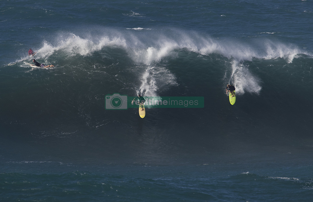 December 13, 2017 - Waimea Bay, Hawaii - Professional surfer John John Florence of Hawaii, right (green board) drops in on a large wave at Waimea Bay. The big wave surfing spot only breaks in the winter when storms send large north swells toward the North Shore of Oahu. (Credit Image: © Erich Schlegel via ZUMA Wire)