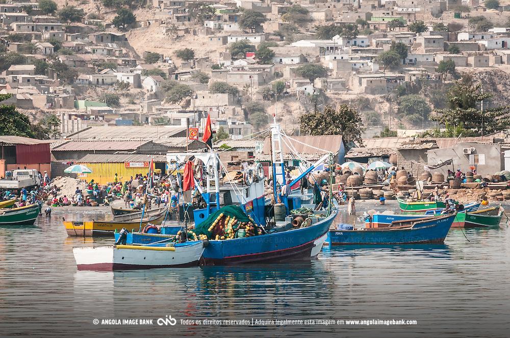 Em primeiro plano - um mercado de peixe e barcos de pesca na baía do Lobito; em segundo plano - os morros com musseques. Província de Benguela, Angola