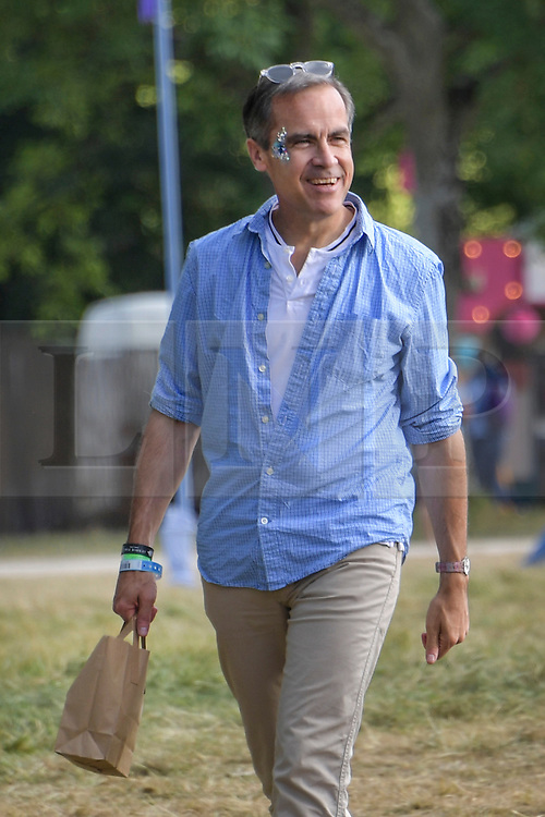 © Licensed to London News Pictures. 05/08/2016. WILDERNESS FESTIVAL, CORNBURY PARK, OXFORDSHIRE, UK.  Mark Carney, Governor of the Bank of England buys a Che Guevara T shirt at the Wilderness Festival. .  Photo credit: MARK HEMSWORTH/LNP