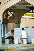 22 DECEMBER 2012 - SINGAPORE, SINGAPORE: Men perform ablutions, the ritual washing and cleansing Muslims do before entering a mosque for prayers, at the Sultan Mosque in Singapore. The Sultan Mosque is the focal point of the historic Kampong Glam area of Singapore. Also known as Masjid Sultan, it was named for Sultan Hussein Shah. The mosque was originally built in the 1820s. The original structure was demolished in 1924 to make way for the current building, which was completed in 1928. The mosque holds great significance for the Muslim community, and is considered the national mosque of Singapore. It was designated a national monument in 1975.           PHOTO BY JACK KURTZ