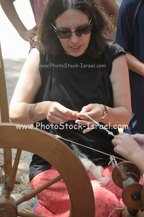 Mature Caucasian woman spinning combed cotton into a thread a traditional spinning wheel is on the left