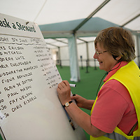 A woman volunteer writing out changes to the events timetable at The Hay Festival of Literature and the Arts, Hay on Wye, Powys, Wales UK, Sunday June 05 2016<br /> <br /> Picture by Keith Morris/Writer Pictures