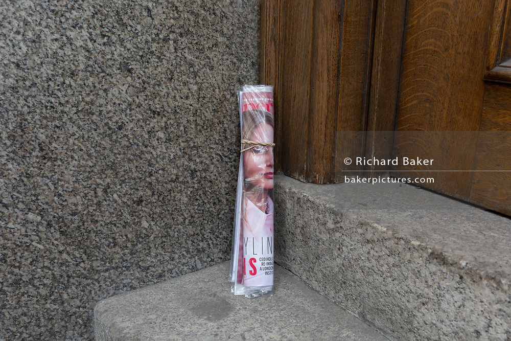The face on the cover of a rolled-up magazine is propped up on the steps of an office in the City of London, on 23rd April 2018, in London, England.