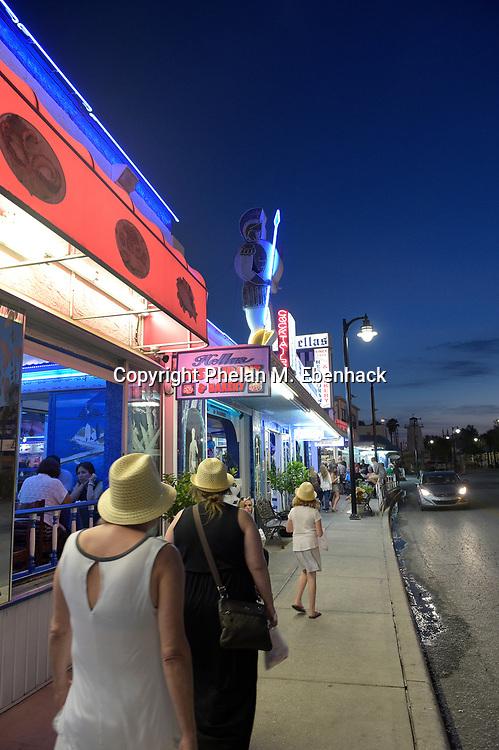 Pedestrians walk past diners eating at Greek restaurants in the Sponge Docks district in Tarpon Springs, Fla., Saturday, April 4, 2015. (Photo by Phelan M. Ebenhack)
