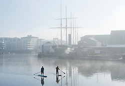 © Licensed to London News Pictures; 27/02/2021; Bristol, UK. People on paddle boards take exercise around Bristol Harbourside and past the SS Great Britain on a misty morning while in lockdown during the covid-19 coronavirus pandemic. The forecast is for bright sunny weather. Photo credit: Simon Chapman/LNP.