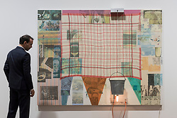 "© Licensed to London News Pictures. 28/11/2018. LONDON, UK. A staff member views Rumor (Spread), 1980. Preview of ""Robert Rauschenberg: Spreads, 1975-83"", the first UK exhibition dedicated to the American artist's Spreads series.  Twelve key works, the largest of which stretches to over six metres wide, are on view together with paper collages that relate to the Spreads series.  The works are on display at Galerie Thaddaeus Ropac's gallery in Mayfair from 28 November to 26 January 2019.  Photo credit: Stephen Chung/LNP"