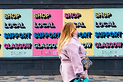 Glasgow, Scotland, UK. 26 October 2020. View of Glasgow city centre on weekday during circuit breaker lockdown with bars and restaurants closed. Pictured; Woman walks past billboard asking for support for local Glasgow shops  . Iain Masterton/Alamy Live News