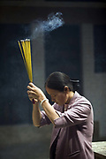 A woman lights incense at the Thien Hau Pagoda, Ho Chi Minh City (formerly Saigon), Vietnam