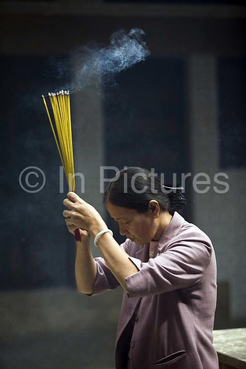A woman lights incense at the Thien Hau Pagoda, Ho Chi Minh City (formerly Saigon), Vietnam