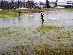 © London News Pictures. 28/02/2014. Worcester, UK.  Member of the Environment Agency rescue fish  trapped on Worcester racecourse when flood waters subsided. Fish, including roach, perch, bream and pike, some weighing over 10lbs, were caught using a large hand net. Photo credit: LNP