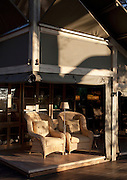 A low sun illuminates the lounge at Abu Camp, a luxury safari camp in the Okavango Delta, Botswana