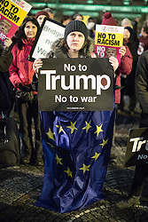"© Licensed to London News Pictures . 20/02/2017 . Manchester , UK . Woman wearing a European Union flag and holding a "" No to Trump "" poster . Hundreds of protesters at a Stop Trump demonstration in Albert Square , central Manchester , to coincide with Parliament debating a petition calling for the government to cancel a State Visit by US President Donald Trump . Photo credit: Joel Goodman/LNP"
