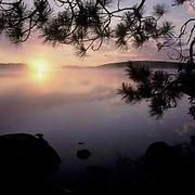 Quetico Provincial Park, Canada. Morning sunrise breaks horizon, Quetico Lake.