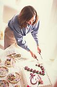 Engaged woman age 27 cutting wedding shower cake.  Minneapolis  Minnesota USA