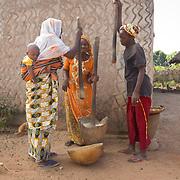 Three women lend a rhythm to compound life, pounding millet. Koumbadiouma, Kolda, Senegal.