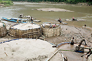 Extracting sand from the Nam Ou river for the building industry, Hatsa, Phongsaly province, Lao PDR. River water is pumped into the large bamboo containers and after the water flows out the sand is dug out and transported by lorry to local construction sites.