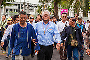 16 MAY 2014 - BANGKOK, THAILAND: Thai anti-government leader SUTHEP THAUGSUBAN (center blue shirt) and his supporters walk to the parliament building in Bangkok. Thousands of protestors from the People's Democratic Reform Committee (PDRC) surrounded the Thai Parliament complex Saturday to pressure the Thai Senate to select an interim Prime Minister to replace ousted former PM Yingluck Shinawatra. The Senate decided not to appoint an interim PM of their own and announced a meeting with the current interim Prime Minister. The protestors left the parliament complex and threatened to return in larger numbers if the Senate doesn't act. The Senate appointment of an acting PM could plunge Thailand into chaos since there is already an interim Prime Minister from the ruling Pheu Thai party.     PHOTO BY JACK KURTZ