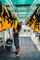 Putting on PFD (life jacket), Wilderness Explorer (small cruise ship), Nakwasina Sound,  Inside Passage, Southeast Alaska USA.