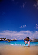 A couple native to the British Virgin Islands embrace on the beach