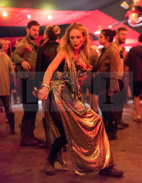 © Licensed to London News Pictures. 27/06/2015. Glastonbury Festival, UK.  Night time Festival atmosphere at Glastonbury Festival 2015 on Saturday Day 4 of the festival in The Unfair Ground area - festival goers dancing.  This years headline acts include Kanye West, The Who and Florence and the Machine, the latter being upgraded in the bill to replace original headline act Foo Fighters. Photo credit: Richard Isaac/LNP