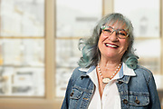 Mature women with blue hair in office face expression smiling.