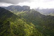 Patches of sun light up a lush valley on the island of Kauai, Hawaii.