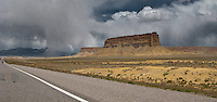storm clouds drop streams of rain in the distance beyond mesas along highways US 491/US 160 in northwesten New Mexico near the Colorado state line.  panorama