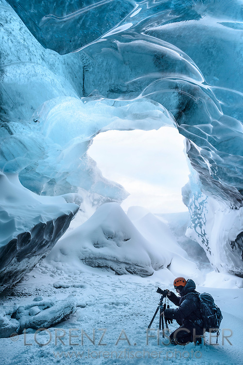 A photographer in an ice cave at the snout of the glacier Breidamerkurjoekull close to the glacier lagoon Joekulsarlon in wintertime, Iceland