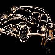 A young boy painting with light to create a VolksWagen beetle shape using the light trails from a sparkler.