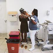 INDIVIDUAL(S) PHOTOGRAPHED: Cheriza Josie. LOCATION: Sacré-Cœur Hospital, Milot Commune, Cap-Haïtien, Haïti. CAPTION: Nurse Cheriza Josie, weighs a mother and her child in the emergency room of Sacré-Cœur Hospital.