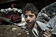 """Young plastic bottles collector in Mokattam. Classification of different types of plastic in Mokattam.The quarry was originally located where the settlement of Mokattam, is now used for storage of paper and aluminum.On the outskirts of Cairo in the middle of Manshiet Nasr neighborhood is located Mokattam settlement known as """"Garbage City"""" is inhabited by Zabbaleen, a community of about 45,000 Coptic Christians living for decades to recycle waste generated by the Egyptian capital: plastic, aluminum, paper and organic waste transformed into compost. Most part of the Association for the Protection of the Environment (APE), an NGO that works in the area, whose objectives are to protect the environment and improve the livelihoods of garbage scavengers in Cairo. According to the UN, the work is done in Mokattam is one of the ten best examples of world environmental improvement. El Cairo , Egypt, June 2011. ( Photo by  Jordi Camí )."""