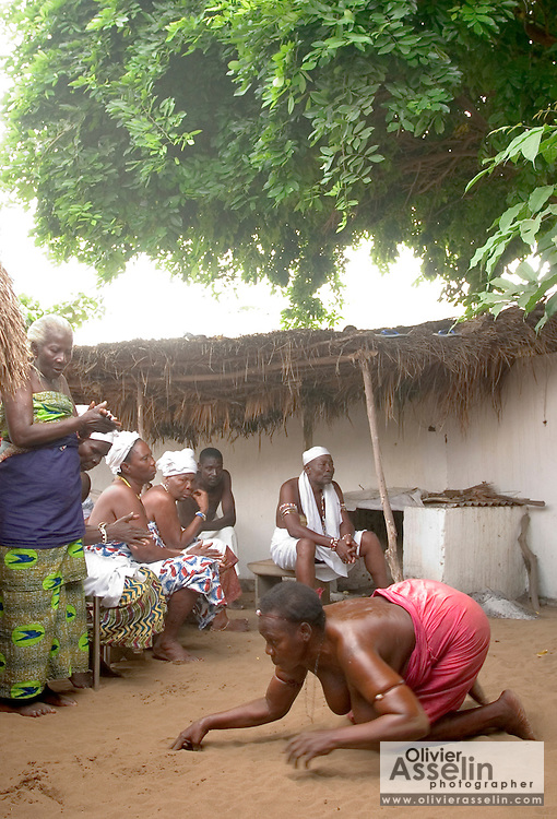 """Shrine servant possessed by spirits during a """"coming out"""" ceremony at a fetish shrine in Aflao, Volta Region, Eastern Ghana. A woman was released after spending three months in a small, dark room, hoping that she'd then be able to find a husband. Despite most Ghanaians being adamant followers of christianism or islam, many of them still maintain traditional beliefs. When facing a problem of any nature, some people will visit a local fetish shrine, looking for help. The main priest will consult the oracles and tell the person in need what has to be done for the problem to go away. People will typically be asked to """"serve"""" the shrine for weeks, sometimes months, as their families pay the priest for their upkeep."""