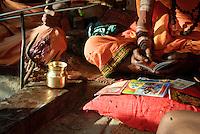 Hindu holy men playing chimta and chanting at the ghats in Varanasi, Uttar Pradesh, India