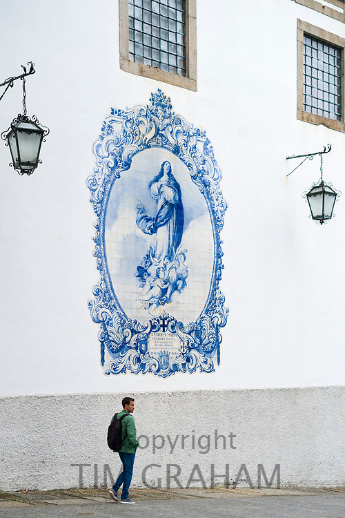 Young man passing blue and white azulejos ceramic tiles of Convent Church of Carmo in Guimaraes in Northern Portugal