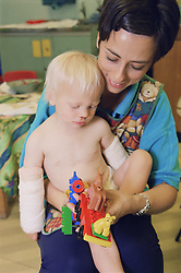 Child with bandaged arms and nursery nurse playing with lego in hospital playroom,