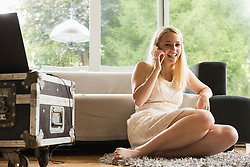 Beautiful young woman talking on mobile phone in the living room, Munich, Bavaria, Germany