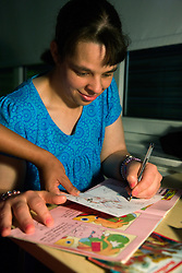 Day Service user with learning disability signing a card,