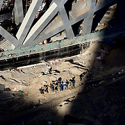 """Construction workers in Beijing pull a metal pipe as they build the """"Bird's Nest"""" National Stadium, which will be unveiled for the 2008 Summer Olympics."""