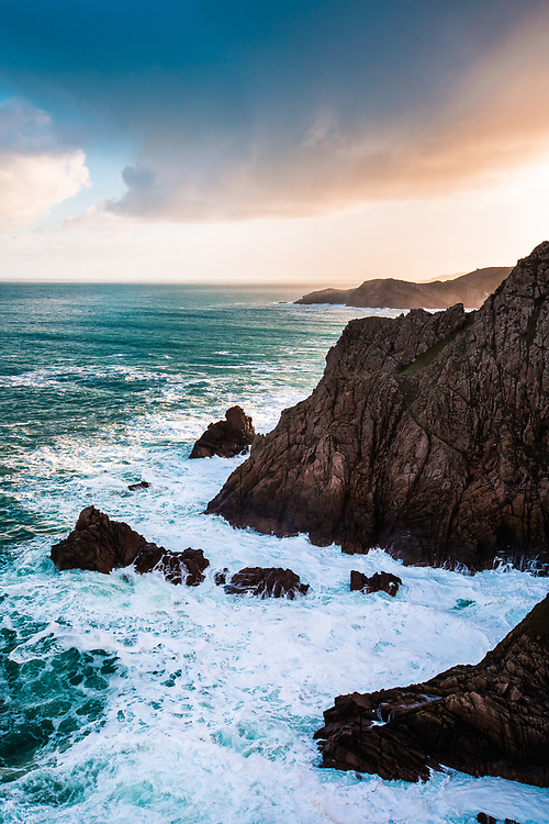 Orange sunlight shining over the cliffs and headland onto the sea along the coastline of Jersey, CI
