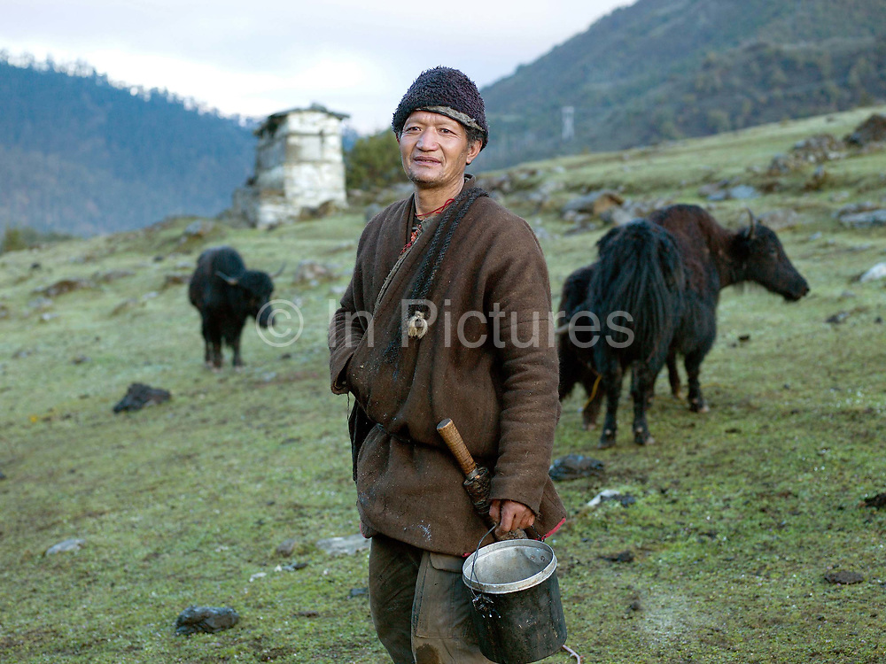 Portrait of a Brokpa yak herder wearing a yak hair 'gho' (traditional tunic') after milking his yaks in a meadow outside the village of Merak, Eastern Bhutan. The Brokpa, the semi-nomads of the villages of Merak and Sakteng are said to have migrated to Bhutan a few centuries ago from the Tshona region of Southern Tibet. Thriving on rearing yaks and sheep, the Brokpas have maintained many of their unique traditions and customs.