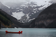 A few red canoes at Lake Louise, in Banff National Park, in foggy, rainy weather