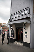 Street scene as men stand smoking outside the Bullring Tavern pub in Birmingham, United Kingdom.
