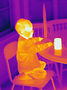 A Thermogram of a boy playing with a model rocket while he drinks hot coco.  A Thermogram of a boy with glasses.  This image is part of a series.  The different colors represent different temperatures on the object. The lightest colors are the hottest temperatures, while the darker colors represent a cooler temperature.  Thermography uses special cameras that can detect light in the far-infrared range of the electromagnetic spectrum (900?14,000 nanometers or 0.9?14 µm) and creates an  image of the objects temperature..