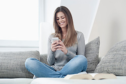 Portrait of smiling young woman with smartphone sitting on couch at home