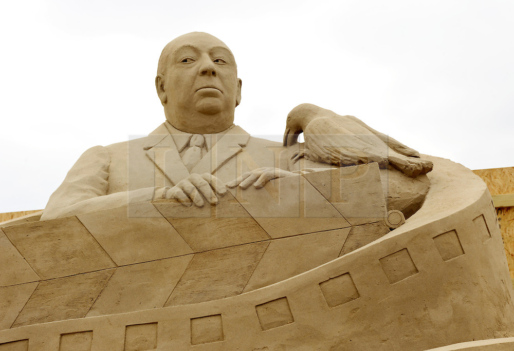 © Licensed to London News Pictures. 26/03/2013. Weston-super-Mare, UK.  Sand sculptor Pedro Mira sculptures of Audrey Hepburn and Alfred Hitchcock.  The Sand Sculpture Festival at Weston-super-Mare beach.  This year's theme is Hollywood with sculptors from around the world working on film icons carved out of sand.  The festival opens to the public from 29 March.  26 March 2013..Photo credit : Simon Chapman/LNP