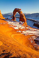 The iconic view of Delicate Arch in Arches National Park in Utah at sunset with the La Sal Mountains in the background.