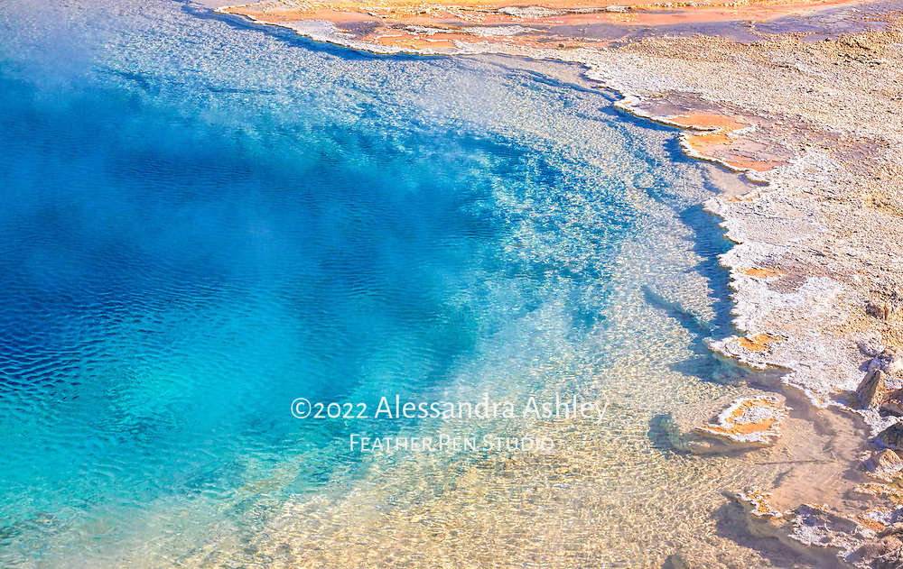 Deep blue sparkling geothermal pool bordered by jagged shoreline. Yellowstone National Park, Wyoming.